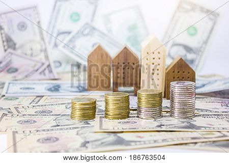 coins home model with banknotes 10 dollar 50 dollar for realestate business and financial concept.