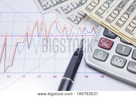 fountain pen calculator with banknotes 10 dollar 50 dollar for business and financial concept.