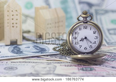 Classic pocket watch and home model on dollar banknote concept and idea of time value and money realestate business and finance concepts.