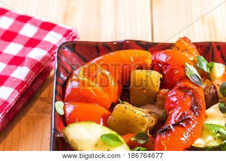 Side dish of roasted veggies on a plate at the bbq picnic table