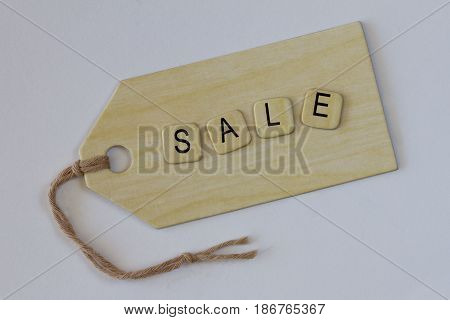 A brown for sale sign on a tag.