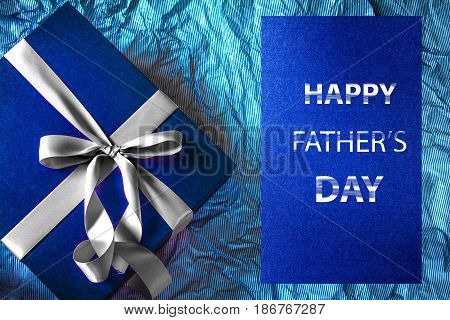 Dark blue gift box with ribbon decoration and Happy Father's Day message on polka blue paper Father's Day concept top view and overhead shot