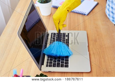 Cropped shot of charwoman dusting with small broom keyboard