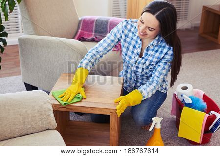 Mid shot of charwoman carefully cleaning with mop small coffee table