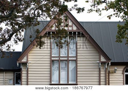Wooden church window with overhanging tree branches