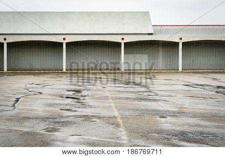 Rain over empty parking lot of a shut down shopping mall