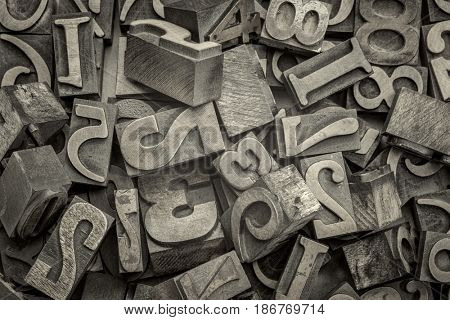 numbers abstract - background of random letterpress wood type printing blocks, top view, black and white platinum toned image
