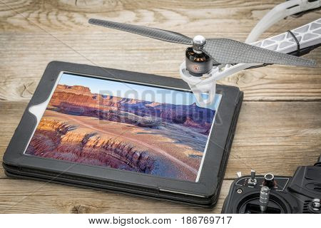aerial photography concept - reviewing pictures of Colorado River canyon near Moab, Utah,  on a digital tablet with a drone rotor and radio controller, screen picture copyright by the photographer