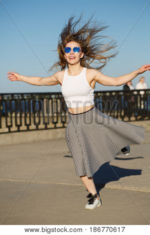 Young attractive girl hipster dancing on the town pier. She is dressed in a top skirt and sunglasses. Flying hair. The concept of life in motion.