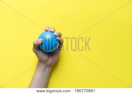 woman holding stress ball on yellow background