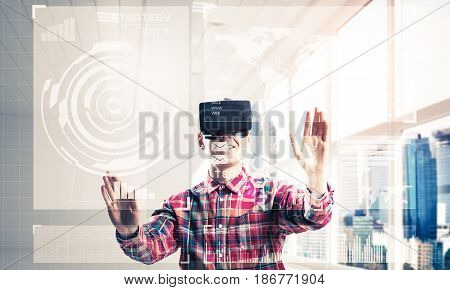 Guy wearing checked shirt and virtual headset working with media screen panel