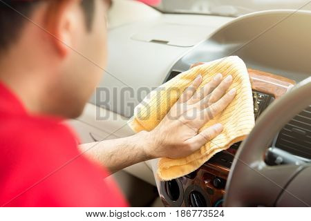 A man cleaning car interior with microfiber cloth - auto detailing and valeting concept