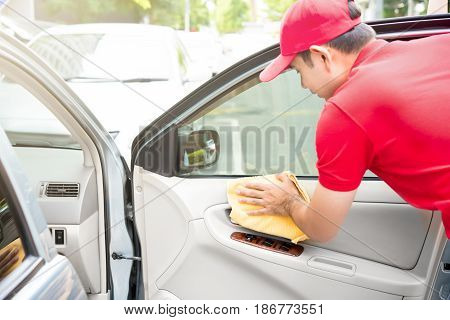 Auto service staff cleaning car door interior panel with microfiber cloth - car detailing and valeting concept