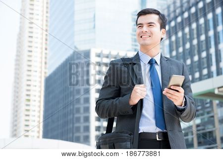 Smiling businessman using mobile phone while carrying bag and walking in the city - business travel and mobile roaming concepts