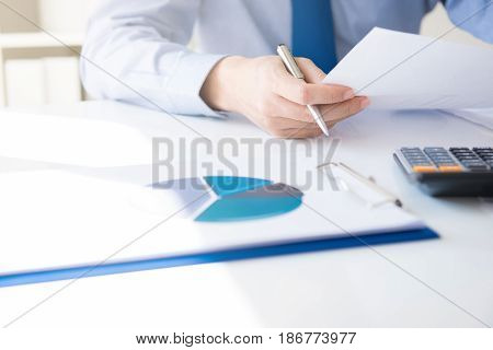 Businessman holding and looking at document on his desk - financial analysis and evaluation concept
