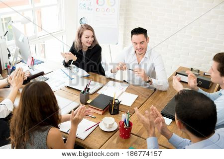 Business people giving their colleague the applause at the meeting in creative office