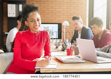 Casual Afro-Caribbean business woman in meeting room of interior design company with interracial colleagues