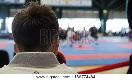 Back view of a young athlete in a white kimono who sits back in the frame, watching the competition in karate adult athletes.
