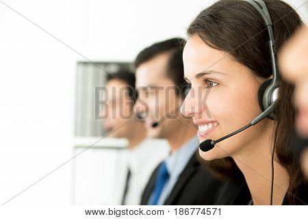 Smiling call center (or telemarketer) staff working in the office