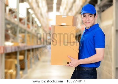 Smiling delivery man carrying boxes on blur warehouse background