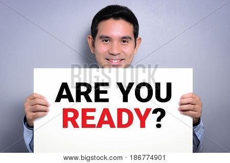 ARE YOU READY? message on white cardboard held by smiling man