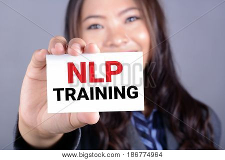 NLP TRAINING message on the card held by a woman