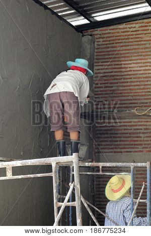 Image of a construction worker mixing cement.cement on April 20, 2017.
