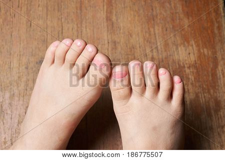 daughter painting little toenails with wooden background