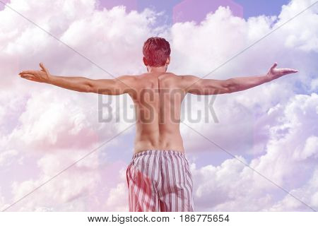 Rear view of shirtless young man standing arms outstretched against cloudy sky