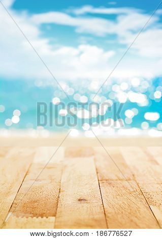Wood table top on blur summer beach and sunny sky background - can be used for display or montage your products