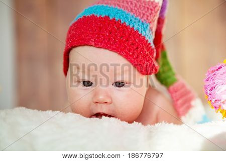 Beautiful two-month-old girl in a red hat. Close-up portrait
