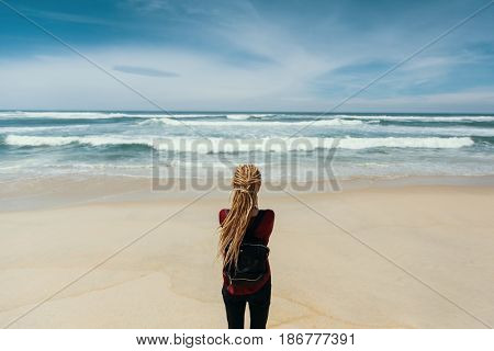 Girl with blonde dreadlocks standing on shore watching the ocean.