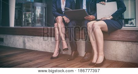 Portrait of businesspeople sitting with laptop in office premises