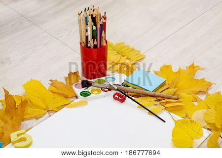 Watercolors, brushes, colored pencils, an album for drawing among maple and ashberry autumn yellow leaves on a wooden background