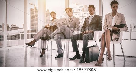Well dressed business people sitting together in waiting room at office