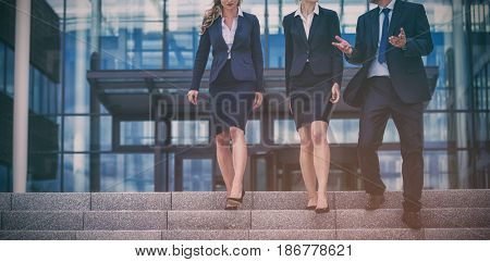 Businesspeople climbing down steps in office premises