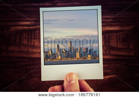 Polaroid Postcard Photograph Of Melbourne Skyline From Waterfront Held By Male Hand Over Wooden Tabl