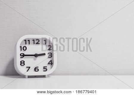 Closeup white clock for decorate show a quarter to three o'clock or 2:45 p.m. on white wood desk and cream wallpaper textured background in black and white tone with copy space