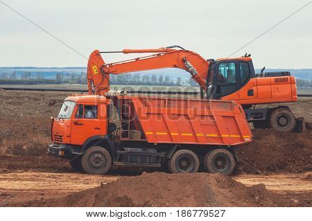 Red excavator loading dumper truck at construction of the road, telephoto