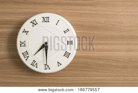 Closeup white clock for decorate show half past seven o'clock or 7:30 a.m. on wood desk textured background with copy space