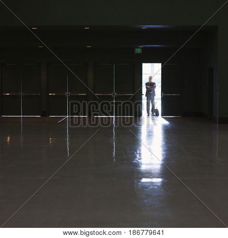 Caucasian businessman standing in doorway of empty room