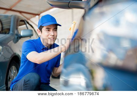 A man polishing (cleaning) car auto detailing or valeting concept