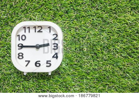 Closeup white clock for decorate show a quarter to three o'clock or 2:45 p.m. on green artificial grass floor textured background with copy space