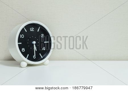 Closeup black and white alarm clock for decorate show show half past four o'clock or 5:30 p.m. on white wood desk and cream wallpaper textured background with copy space