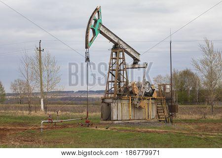Oil pump near highway in Tatarstan, Russia, telephoto