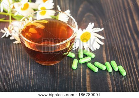 Herbal tea in a transparent cup capsules and chamomile flowers on wooden table. The concept of alternative medicine and phytotherapy.