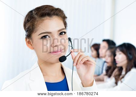 Smiling woman wearing microphone headset as an operator telemarketer call center and customer service staff