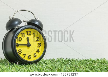 Closeup black and yellow alarm clock for decorate show a quarter to twelve o'clock or 11:45 a.m. on green artificial grass floor and cream wallpaper textured background with copy space