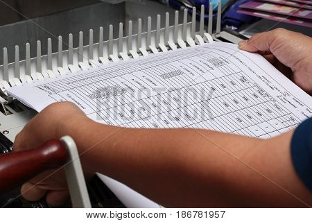 Binding documents with plastic ring binder by using ring binding machine for report preparation. poster