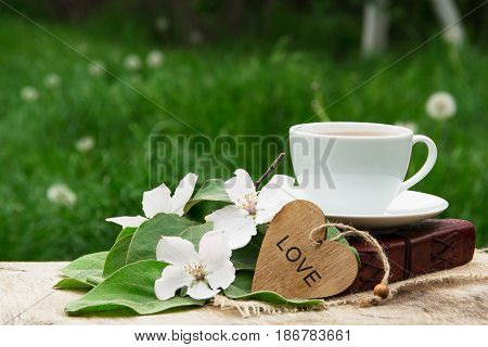 A cup of black tea a book and a branch of a blossoming apple tree. Apple blossom heart and fragrant tea.